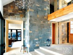 In this lofty foyer, custom stonework by Avignon Stone reflects Colorado's rugged terrain. PHOTO BY Gibeon Photography