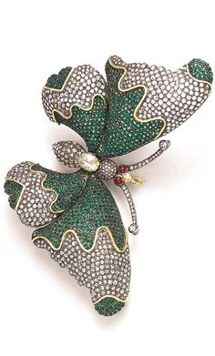 A TSAVORITE GARNET, DIAMOND AND RUBY BUTTERFLY BROOCH The pavé-set diamond body, centering upon a pear-shaped rose-cut diamond, enhanced by cabochon ruby eyes and rose-cut diamond antennae, extending sculpted pavé-set diamond and tsavorite garnet wings, with polished gold stylized veining, mounted in silver and gold, (with concealed hoops for suspension)