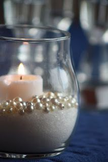 Super easy and budget-friendly wedding centerpiece idea! White sand (or sugar), fake white pearls and a candle.
