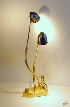 DIE ZWEI Die Leuchte entstand aus einem antiken Messingbügeleisen, auf dem zwei Schwanenhälse und Teile einer ausgemusterten Deckenlampe verschraubt sind. Auf den Lampenschirmen habe ich Überwurfmuttern als Kopfschmuck angebracht. Im Bügeleisen befindet sich ein 12 V Netzteil.