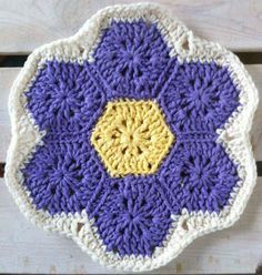 """Grandmother's Flower Garden Dishcloth Skill: Easy Size: About 9"""" diameter Materials: Worsted Weight Cotton Yarn: Purple – 1½ oz, 75 yds (45 g, 68 m) Yellow – 1 oz, 50 yds (30 g, 45 m) Beige – 1 oz, 50 yds (30 g, 45 m) (Lily Sugar 'n Cream – Hot Purple, Yellow, Soft Ecru) Crochet Hook: Size H-8 (5.00 mm) Medallions (Make 7 – 1 Yellow, 6 Purple) Rnd 1: (Right Side) Starting at center, ch 4, sl st in first ch to"""