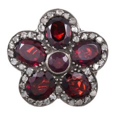 """Victorian Garnet and Diamond Cluster Flower Ring. Silver over yellow gold ring with garnet """"petals"""" fashioned into a flower shape and decorated with rose cut diamonds. Measuring an inch in diameter from the top, this s a fun piece to wear and is large enough to wear as a daytime fashion ring or a more formal cocktail ring.  c 1890"""