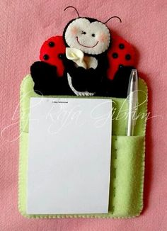 scissors where pen is, needle case where pad of paper is, pin cushion where lady bug is, ... just how to make it stand? also somewhere for spool of thread? for thimble? attach a small fabric/felt bowl/box?