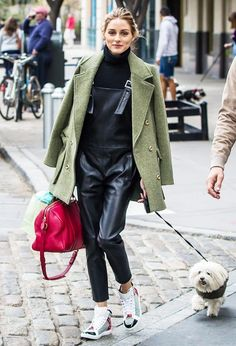 Olivia Palermo wears a turtleneck, leather overalls, olive green peacoat, high-top sneakers, and a red Louis Vuitton duffle bag