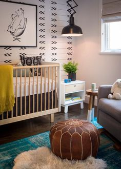 Black and white arrow-printed wallpaper sets the tone for this eclectic, mature nursery. A turquoise, over-dyed rug brings a playful pop of color to the neutral space. Scandinavian-style furniture is both sleek and gender-neutral.