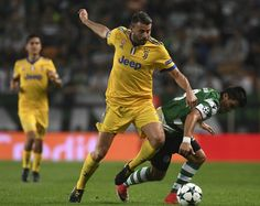 Juventus' defender Andrea Barzagli (L) vies with Sporting's Argentinian forward Marcos Acuna during the UEFA Champions League football match Sporting CP vs Juventus FC at the Jose Alvalade stadium in Lisbon on October 31, 2017. / AFP PHOTO / FRANCISCO LEONG