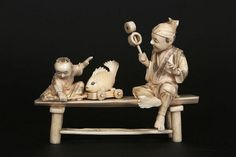 A JAPANESE IVORY OKIMONO Carved as a man sitting on a table with a child pulling a toy fish, signed. 15cm wide