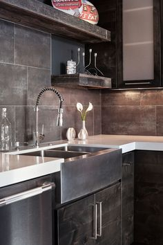 The backsplash is a porcelain, 10x20 tile with a metallic finish. It's trimmed on the sides with metal Schluter trim. Dal Tile Metal Effect & Dal Tile Metal Fusion are a very close match and a quality product.