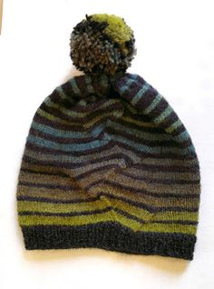 Hat with a twist is a slouchy hat that accompanies the stripes with a twist pullover. It features the same stripes and playful (easy) pattern that makes the stripes go dancing. A large pompom finishes the hat. (Instructions for making a pompom included)