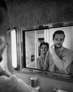 Actress Joanne Woodward watches her husband Paul Newman shave in 1963.