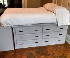 """The only problem is that our new bedroom has no closets. We had some time on our hands and a shop where we could work in temporarily, so we decided to build furniture that would help us out. What we came up with for our bedroom is """"The Dresser Bed.""""The theory is pretty simple. Two low, long dressers under the bed, with bookshelves at the end for further storage. Also, we planned an area und..."""