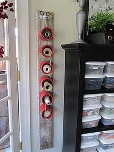 coffee cans bolted to a plank, holding strings and twines. Down the side is a tape measure. At the top, scissor storage. Takes very little space.