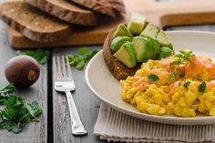 Photo d'une assiette contenant du pain complet avec de l'avocat et une omelette au saumon fumé.
