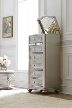 The Havertys Brigitte lingerie chest boasts glam style with a classic silhouette in a platinum finish. Lift the top to reveal an inlaid mirror above a felt-lined jewelry tray.