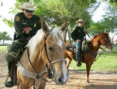 Mounted Border Patrol officers. The palomino horse has a woven breastcollar and green saddlebags.