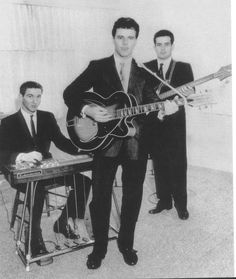 An unusual picture of Ricky Nelson, James Burton and James Kirkland. Burton on Rickenbacker steel guitar, KIrkland was a Rickenbacker bass and Nelson with what appears to be a Rick hybrid Spanish F hole acoustic. Must have been at the Rickenbacker factory.