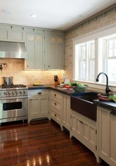 Fantastic kitchen with copper farmhouse sink, exposed brick wall, dark floors, and white accents by cornelia