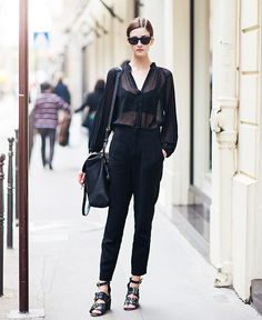Black top, black trousers, black strappy sandals, black bag, and black sunglasses