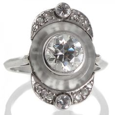 A rare platinum Art Deco French ring featuring a central older brilliant cut diamond of estimated weight 1.25ct graded as colour G clarity SI1 in a bezel mount set within a low circular cabochon style cut rock crystal piece with a short band at either end of each grain set rose cut diamonds centred by a raised diamond all above an underbezel carved in a scrolling style all between a pair of upswept shoulders tapering to a plain polished knife edged band.
