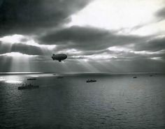 Silhouetted Atlantic convoy ships seem to be ducking the sun's searching spotlight as a US Navy airship reconnoiters overhead in June 1943.