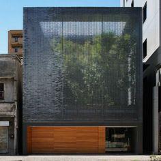 Hiroshi Nakamura & NAP Architects.  Situada em uma área de 330m ² no Centro de Hiroshima, inserida entre dois edifícios altos e de frente a uma via movimentada. Nessa lógica, um jardim se encontra na entrada da casa para trazer o caráter de privacidade, tranquilidade e aconchego. Esse espaço pode ser visto dos quartos. A fachada possui cerca de 6.000 blocos de vidro e funciona como protetor solar e torna possível a passagem da ventilação natural para dentro da casa.