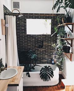 Boho bathroom with dark subway tile shower and wood counter top.  Love all the plants!