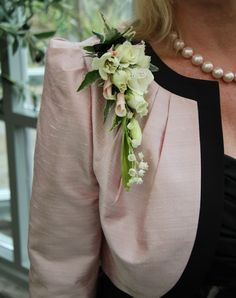 epaulette corsage to tone with her oyster pink and black jacket, we used fresh Rolled Sweet Avalanche Roses, Lily of the Valley, Snowflake Rose Buds and fragrant Freesia
