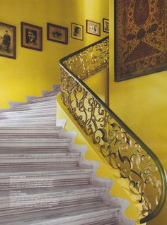 A FLIGHT ABOVE Family photographs & an antique kalamkari textile adorn the walls of the grand staircase, which has a wrought iron banister. The risers of the steps are finished with bevelled marble. Anita Lal's gorgeous New Delhi home featured in November's #ArchitecturalDigest India magazine.