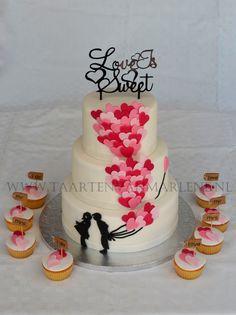 Bruidstaart versierd met hartjes en passende cupcakes