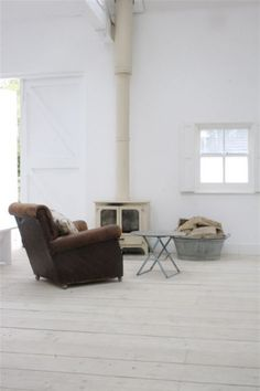 Foster House 'Openview' Kent. Danish white soaped floorboards. White fireplace. White barn doors.