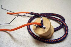 French knitting with cord--wouldn't bother with the spool knitting--would be cute idea to crochet a dark blue outer cover for a bright orange lanyard--Go Illini!!