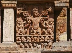 Sun god. He is accompanied by his 2 sisters - Usha and Pratyusha and his charioteer Aruna. For a change i could see Sun god with 2 hands in tact holding the full bloom lotuses at a temple. In Konark at all the places, his hands are vandalized.