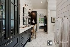 In this master bathroom, rich black cabinets provide plenty of storage and style when combined with the marble hex tile floors and white shiplap on the walls. Black Cabinets Bathroom, Shiplap Bathroom, Best Bathroom Flooring, White Cabinets, Custom Home Builders, Custom Homes, Black And White Master Bathroom, Bathroom Black, Modern Bathroom