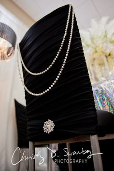 "Our ""Audrey Hepburn"" chair using black Chloe chair covers from Chamaeleon Chairs ornamented with a string of pearls and the diamond brooch. Designed by Creative Weddings Planning & Decor (Photo courtesy of @Christy Swanberg)"