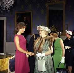Bedecked in flowered hat and big gloves, a White House visitor greets Jackie before a luncheon.