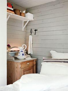 Bredvid sängen står ett ärvt pottskåp med handfat och kanna, på hyllan ovanför har Anna ställt böcker för alla åldrar och några spel av omtanke om gästerna.