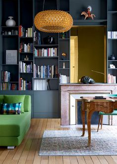 Built-in bookcases painted in dark muted greyish blue paired with antique french writing desk.