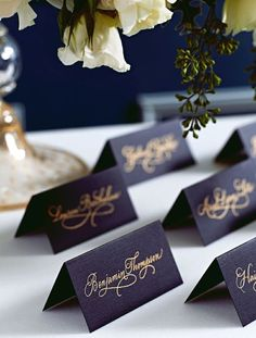 down-this-aisle:  black place cards adorned with golden script