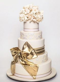 Glamorous white wedding cake wrapped with a gold bow; Featured Cake: Ron Ben-Israel Cakes