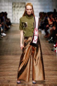 Berlin Fashion Week: Marina Hoermanseder  Natürlich darf auch bei dem glamourösen Look aus goldener, weit ausgestellter Hose und Chiffonbluse die markante Schnalle nicht fehlen – hier als cooler Schal. Die Lederschnalle avanciert bei Hoermanseder zum Symbol ihrer Vision, dass sich die Frauen zusammenschließen.