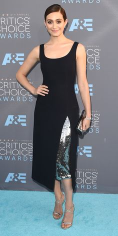 EMMY ROSSUM wears a navy Dior cocktail dress with a high slit inset with a sequin panel, silver Jimmy Choo sandals and a slicked-back bun.