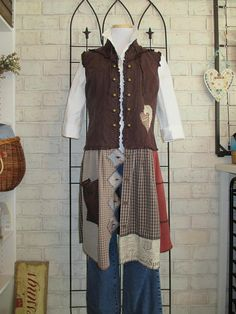 Long bohemian styled vest/jumper. Can be worn with or without jeans. Chocolate brown upcycled cotton vest with added skirt of pre-loved, recycled fabrics in shades of tan, grey, pale salmon and dark brown. (Blouse and jeans shown are not included). Size is medium. Measurements are: --16 across shoulders --bust is 42 --waist is 38 --hips are free --length from shoulder is 40 1/2 Best care for this mixed fabric garment is machine wash warm and gentle, and hang to dry. Garment is fi...