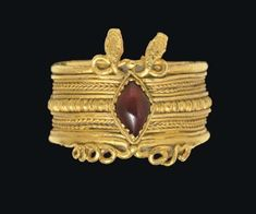 A GREEK GOLD AND GARNET FINGER RING   HELLENISTIC PERIOD, CIRCA 3RD CENTURY B.C.   In the form of two serpents, the broad hoop fabricated from sheet, the outer surface embellished with rows of wires, the serpent heads protruding on one side with their bodies looping in figure-8s, a single granule in between, their tails coiled outward along the other side, the hoop set with a diamond-shaped convex garnet in a dog-tooth setting