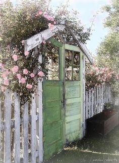 Old door gates and a tall picket fence with roses peeking over ~ protect the roses within while creating a delightful street view.