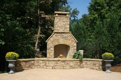 Outdoor Stacked Stone Fireplace With Seating Wall