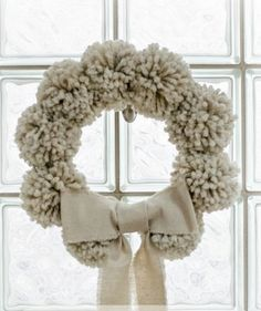Use oatmeal colored yarn to make nine big, fluffy pom poms. Then attach each one to a wreath form that's been wrapped in the same color yarn. To save time, you can purchase pre-made pom poms from nearly any craft store.