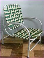 1950s bent aluminum patio chair with green and brown webbed woven seat.