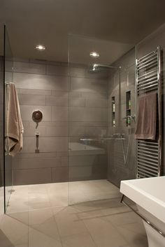 Modern gray shower. Horizontal gray shower tile. Towel warmer. Large curbless shower with glass door.
