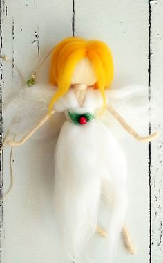 A delicate handmade needle felt fairy. This whimsical fairy is perfect for a Christmas tree decorations or a little girls room. The fairy is made from wool by using needle felt technique. She is hanging on a string with some lovely beads. She is wearing a white gown with a green and red ornament and has a long blond hair. She also has a little sparkle in her wings. Add a little magic to your home with this delicate white fairy!  Dont wait for Christmas - buy this cutie now :)  * Size: This…