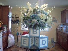 Baby boy shower centerpiece for buffet table.  I bought 3 wood block boxes at hobby lobby and painted them.  Added foam to one and made the flower arrangement. The blocks were 12 x 12 .  The final arrangement was very large and perfect for a baby shower buffet.